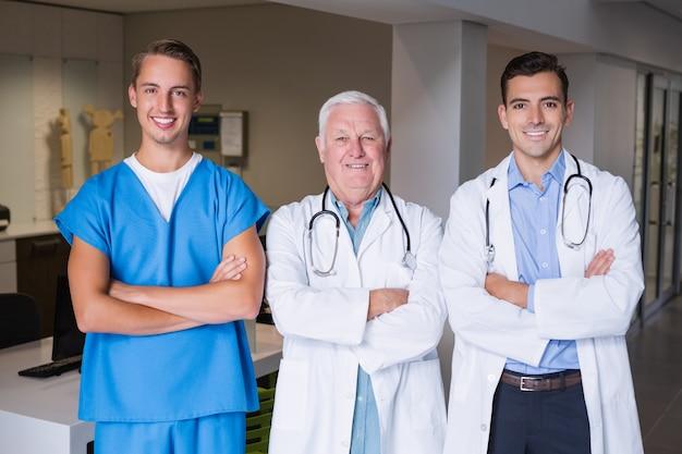 Portret uśmiechnięte lekarki stoi z rękami krzyżować