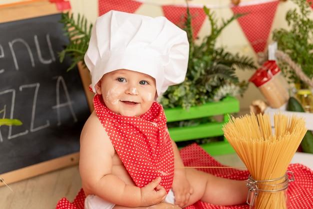 Portret uśmiechnięte małe dziecko w kapeluszu szefa kuchni przygotowuje spaghetti w kuchni