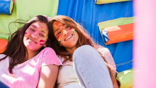 Portret uśmiechnięte młode kobiety z holi koloru farbą na ich twarzy patrzeje kamerę