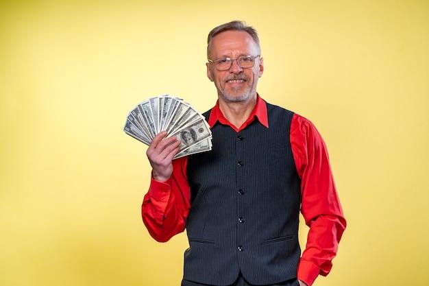 Portret uśmiechnięte szczęśliwe i białe zęby starszy stary biznesowy mężczyzna trzyma pieniądze w rękach