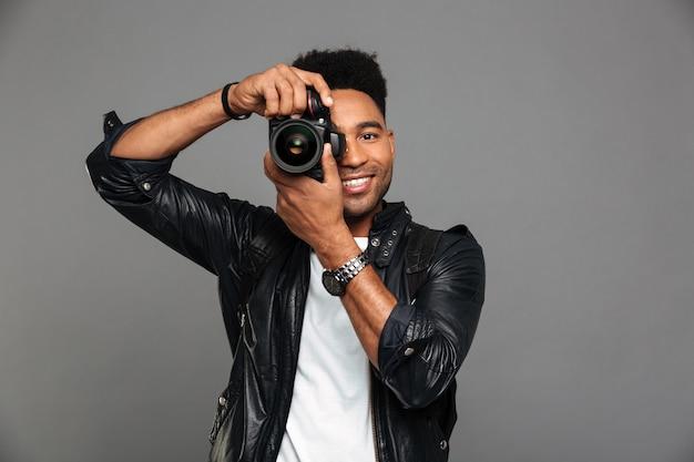 Portret uśmiechniętego afro amerykańskiego faceta w skórzanej kurtce