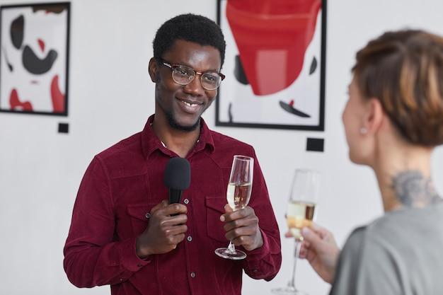 Portret uśmiechniętego afro-amerykańskiego mężczyzny trzymającego mikrofon i przeprowadzającego wywiady z gośćmi podczas otwarcia galerii sztuki