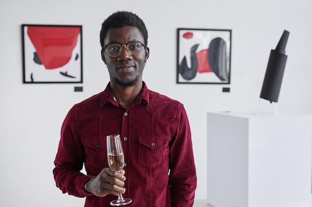 Portret uśmiechniętego afroamerykanina trzymającego kieliszek szampana i pozującego podczas otwarcia galerii sztuki w pasie