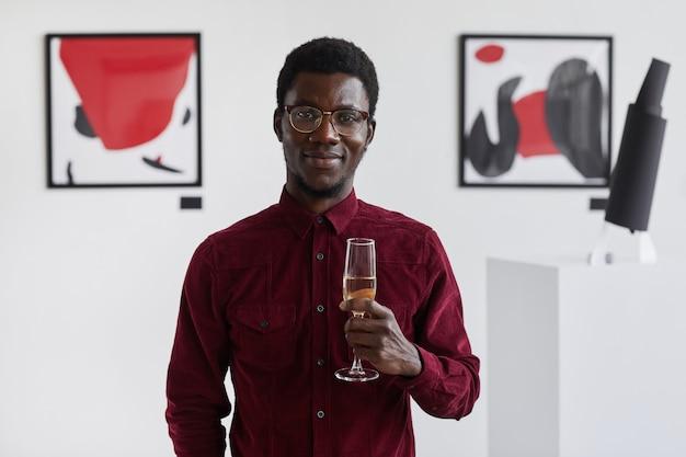 Portret uśmiechniętego afroamerykanina trzymającego kieliszek szampana w pasie i na otwarcie galerii sztuki,