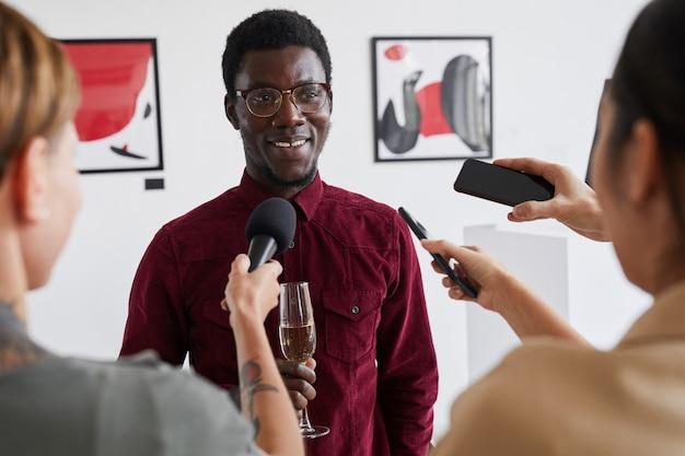 Portret uśmiechniętego afroamerykanina udzielającego wywiadu dziennikarzom podczas otwierania wystawy w galerii sztuki współczesnej