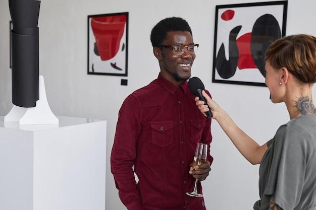 Portret uśmiechniętego afroamerykanina udzielającego wywiadu młodej kobiecie na otwarciu galerii sztuki współczesnej