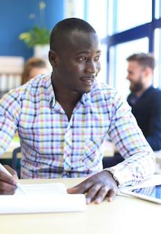 Portret uśmiechniętego afroamerykańskiego biznesmena z kierownictwem pracującym w tle