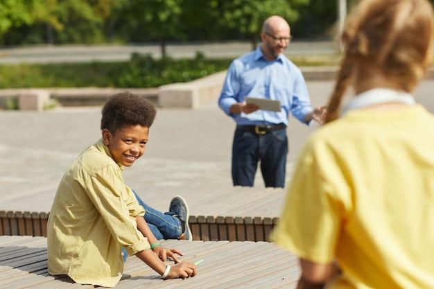 Portret uśmiechniętego afroamerykańskiego chłopca patrząc na kolegę z klasy, ciesząc się lekcją na świeżym powietrzu w słońcu z nauczycielem w tle, skopiuj miejsce