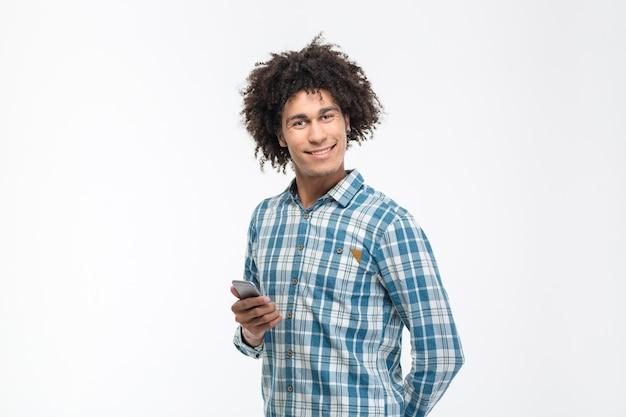 Portret uśmiechniętego afroamerykańskiego mężczyzny trzymającego smartfon i patrzącego na białym tle na białej ścianie