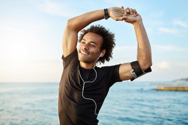 Portret uśmiechniętego afroamerykańskiego sportowca, rozciągającego umięśnione ramiona przed treningiem nad morzem, używając aplikacji muzycznej na swoim smartfonie.