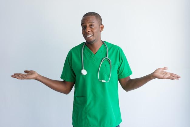 Portret uśmiechniętego amerykanina afrykańskiego pochodzenia doktorska wzrusza ramionami ramiona.