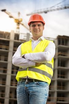 Portret uśmiechniętego architekta w kasku stojącym przed budynkiem w budowie