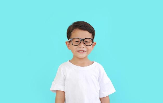 Portret uśmiechniętego azjatyckiego małego chłopca w okularach izolowanych na błękitnym tle