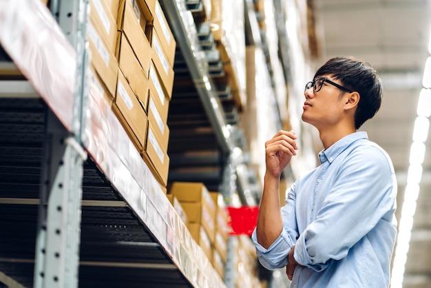 Portret uśmiechniętego azjatyckiego menedżera pracownika stojącego i szczegółów zamówienia sprawdzania towarów i dostaw na półkach