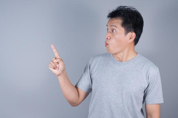 Portret uśmiechniętego azjatyckiego mężczyzny noś szarą koszulkę wskazującą palcem w bok na szarym tle
