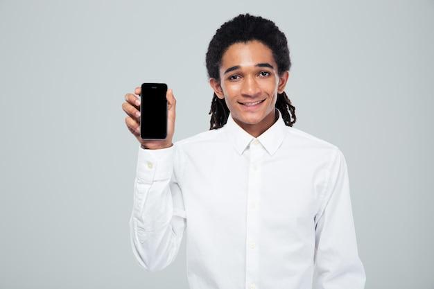 Portret uśmiechniętego biznesmena afro-amerykańskiego pokazano pusty ekran smartfona na szarej ścianie