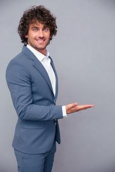 Portret uśmiechniętego biznesmena gospodarstwa copyspace pod ręką na szarej ścianie
