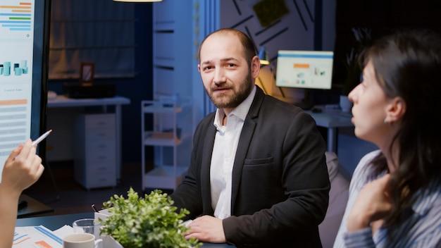 Portret uśmiechniętego biznesmena patrzącego w kamerę pracującego w strategii firmy