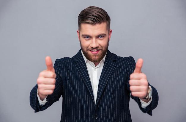 Portret uśmiechniętego biznesmena pokazując kciuk do góry na szarej ścianie