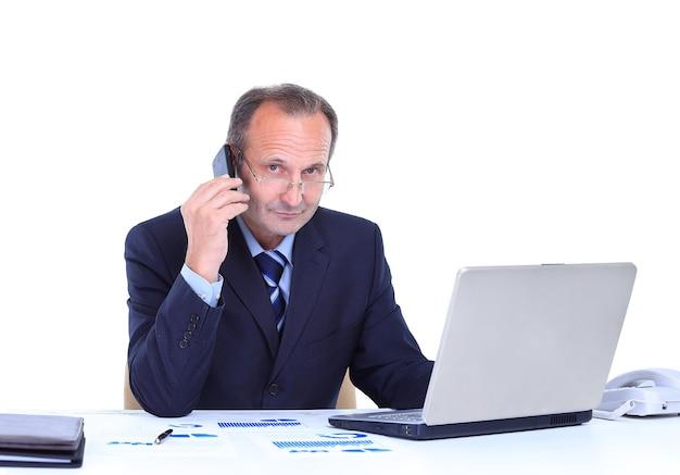 Portret uśmiechniętego biznesmena rozmawiającego przez telefon komórkowy i pracującego na laptopie w biurze