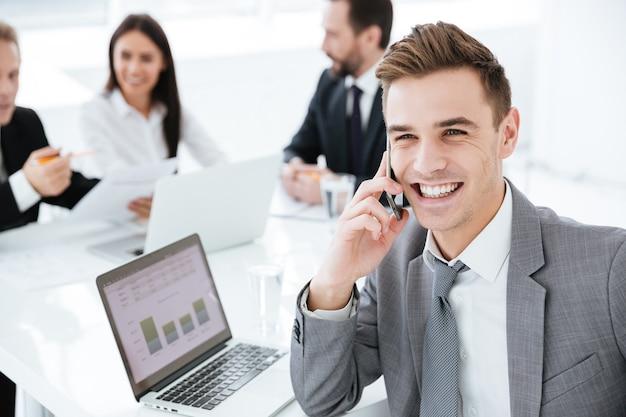 Portret uśmiechniętego biznesmena siedzącego przy stole z kolegami i rozmawiającego przez telefon w biurze