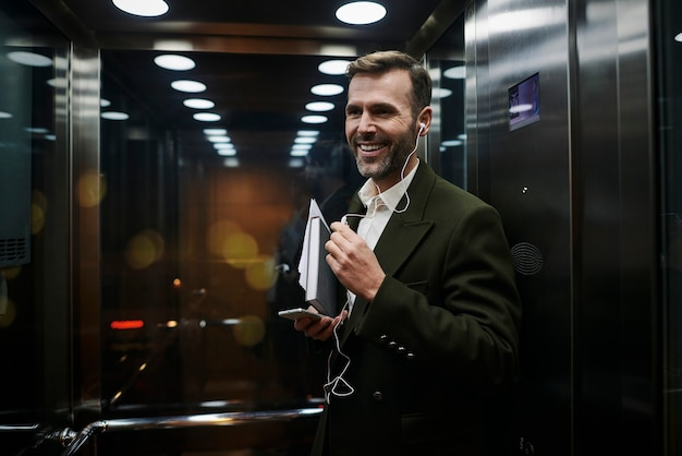 Portret uśmiechniętego biznesmena słuchającego muzyki w windzie