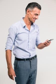 Portret uśmiechniętego biznesmena używającego smartfona na białym tle