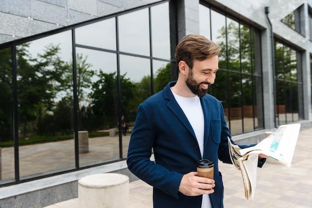 Portret uśmiechniętego biznesmena w kurtce pijącego kawę z papierowego kubka i czytającego gazetę, stojąc na zewnątrz w pobliżu budynku