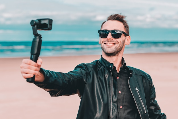 Portret uśmiechniętego blogera w okularach przeciwsłonecznych robiącego selfie lub przesyłającego strumieniowo wideo na plaży przy użyciu kamery sportowej ze stabilizatorem aparatu z gimbalem.