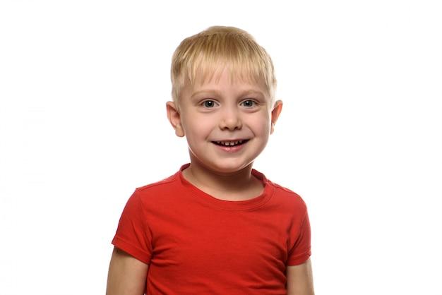 Portret uśmiechniętego blond chłopca w czerwonej koszulce