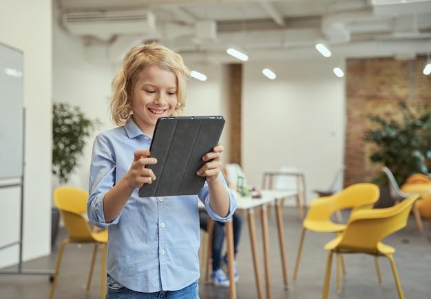 Portret uśmiechniętego chłopca korzystającego z komputera typu tablet podczas pozowania do kamery podczas zajęć macierzystych