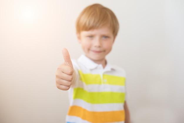 Portret uśmiechniętego chłopca pokazuje kciuki do góry. selektywne ustawianie ostrości