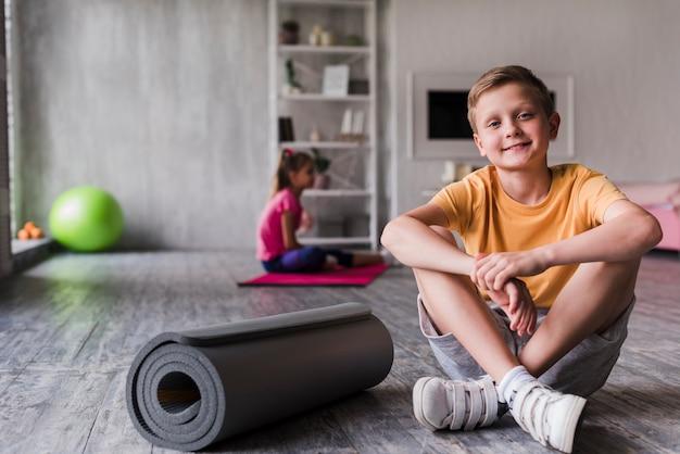 Portret uśmiechniętego chłopca siedzącego w pobliżu zwinięte maty do ćwiczeń