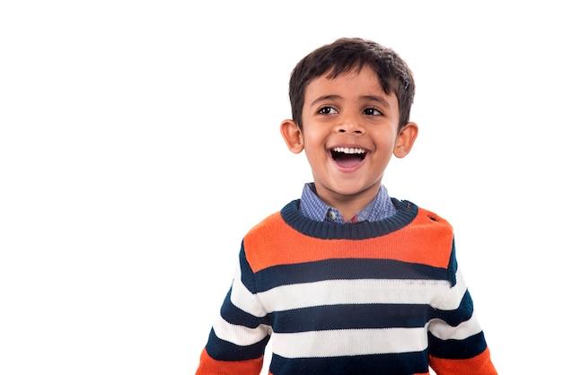 Portret uśmiechniętego chłopca, stwarzających na białej ścianie.