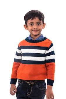 Portret uśmiechniętego chłopca, stwarzających na białym tle.