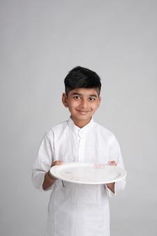 Portret uśmiechniętego chłopca, trzymając w rękach pusty talerz