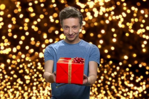 Portret uśmiechniętego chłopca ubranego na co dzień z czerwonym pudełkiem na prezenty