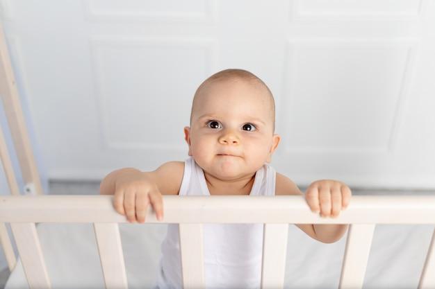 Portret uśmiechniętego chłopca w wieku 8 miesięcy stojącego w łóżeczku dziecięcym w białych ubraniach