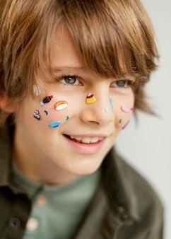 Portret uśmiechniętego chłopca z pomalowaną twarzą
