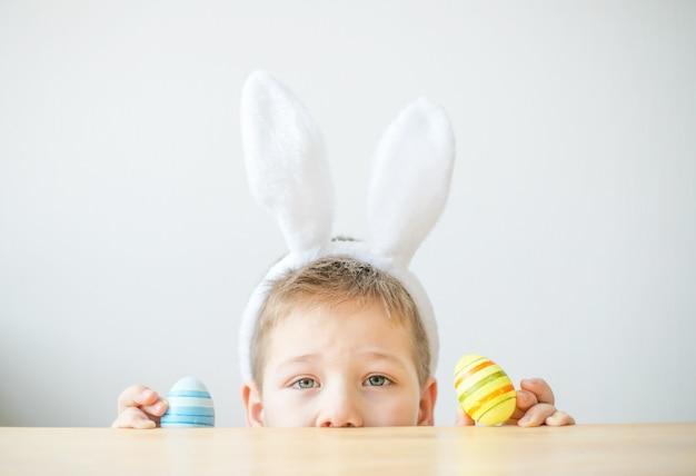 Portret uśmiechniętego chłopca z uszami królika, trzymając kolorowe jaja na wielkanoc w studio sztuki, miejsce. przygotowania do wielkanocy.