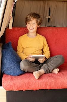 Portret uśmiechniętego chłopca za pomocą tabletu