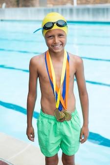 Portret uśmiechniętego chłopca ze złotymi medalami na szyi, stojącego w pobliżu basenu
