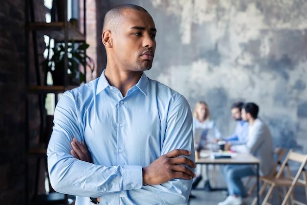 Portret uśmiechniętego człowieka biznesu afroamerykanów z kadry kierowniczej pracujących w tle.