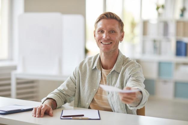 Portret uśmiechniętego człowieka współczesnego wręczanie papierów wyborcy podczas pracy w lokalu wyborczym, miejsce