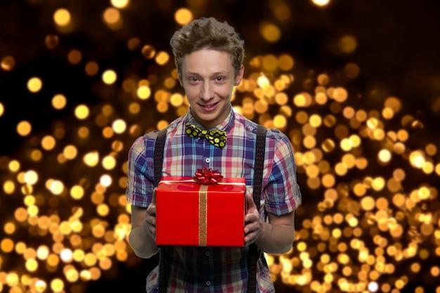 Portret uśmiechniętego dobrze ubranego chłopca z czerwonym pudełkiem. przystojny facet stoi na tle ze świecącymi światłami.