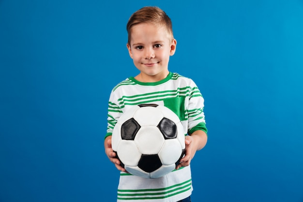 Portret uśmiechniętego dzieciaka mienia piłki nożnej piłka