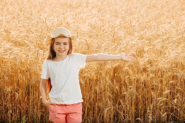Portret uśmiechniętego dzieciaka w kapeluszu stojącego na polu pszenicy z wyciągniętymi ramionami, patrząc na kamerę