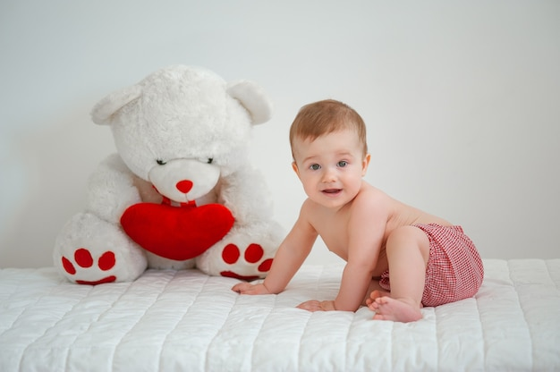 Portret uśmiechniętego dzieciaka z misiem-zabawką na jasnym tle
