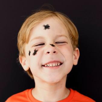 Portret uśmiechniętego dzieciaka z twarzą pomalowaną na halloween