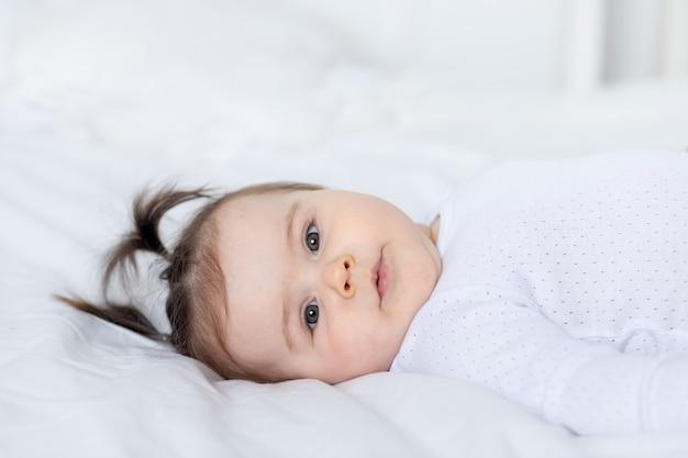Portret uśmiechniętego dziecka na łóżku w domu, koncepcja szczęśliwej kochającej rodziny i dzieci